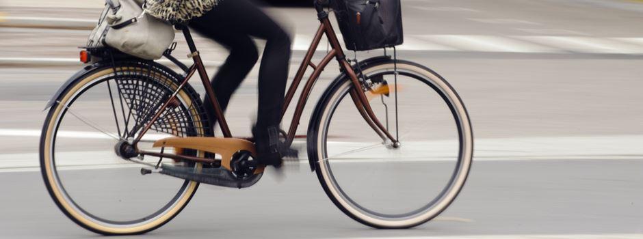 Männer stoßen Frau vom Fahrrad