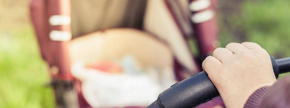 Frau schlägt gegen Kinderwagen mit Baby darin