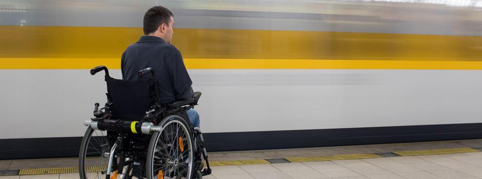 Mann hilft Rollstuhlfahrer, der wegen defektem Aufzug am Bahnsteig festsitzt